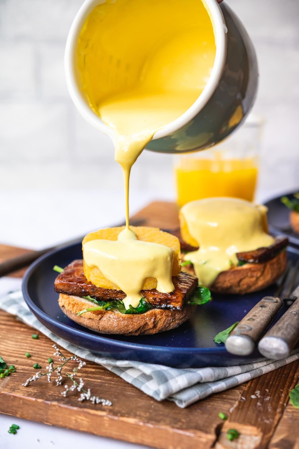 pouring vegan hollandaise sauce onto polenta eggs benedict on blue plate.