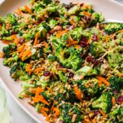 close up side view of vegan broccoli salad with cranberries and sunflower seeds on light pink platter.