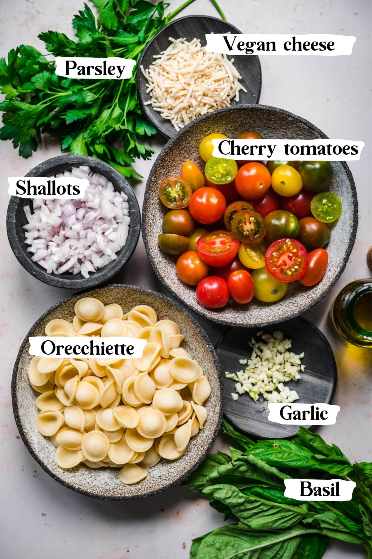 overhead view of ingredients for burst cherry tomato pasta in prep bowls.