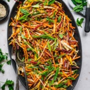 overhead view of shaved rainbow carrot salad with miso sesame dressing on large black platter.