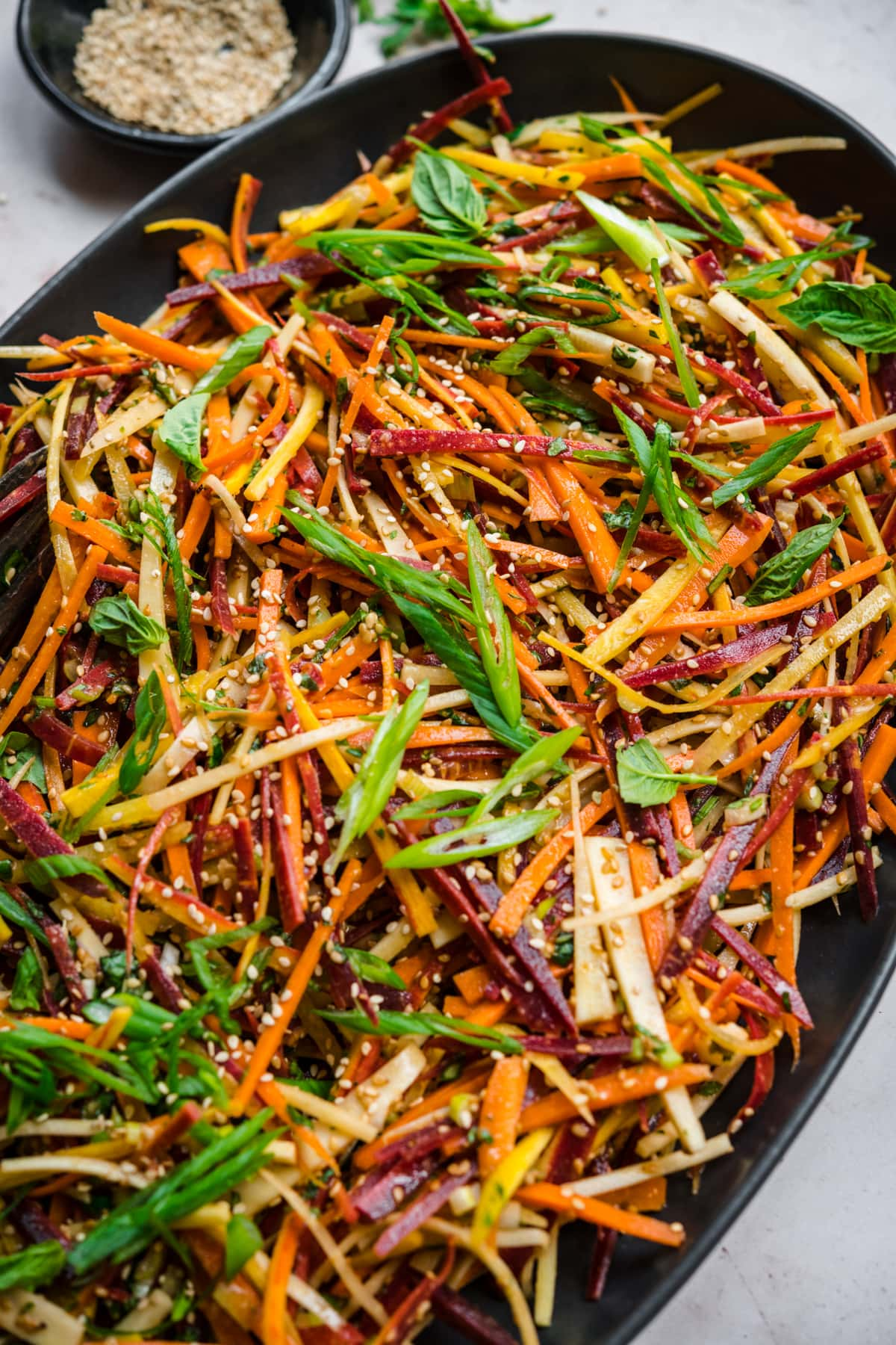 close up view of shaved rainbow carrot salad with miso sesame dressing on large black platter.