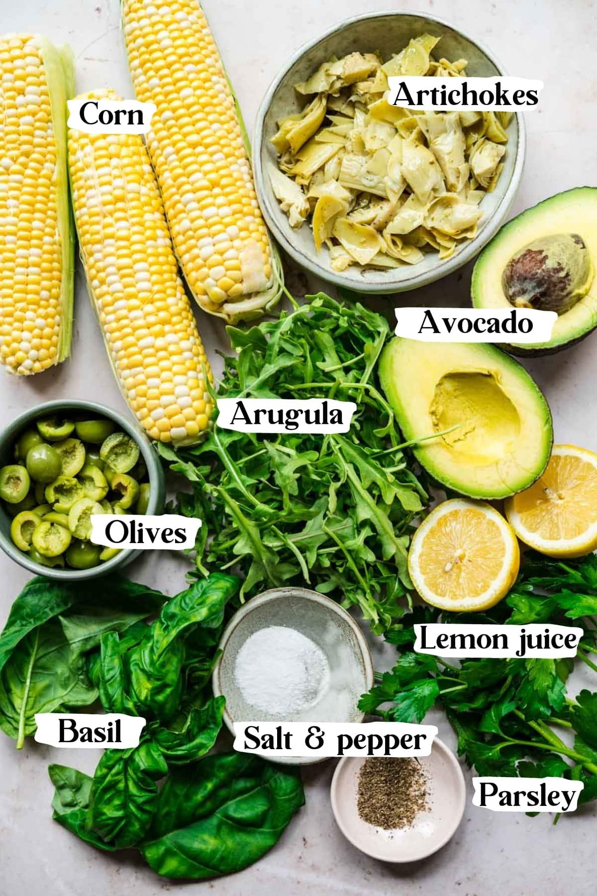 overhead view of ingredients for corn avocado arugula salad.