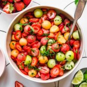 close up overhead view of melon ball salad with strawberries and mint in white bowl.