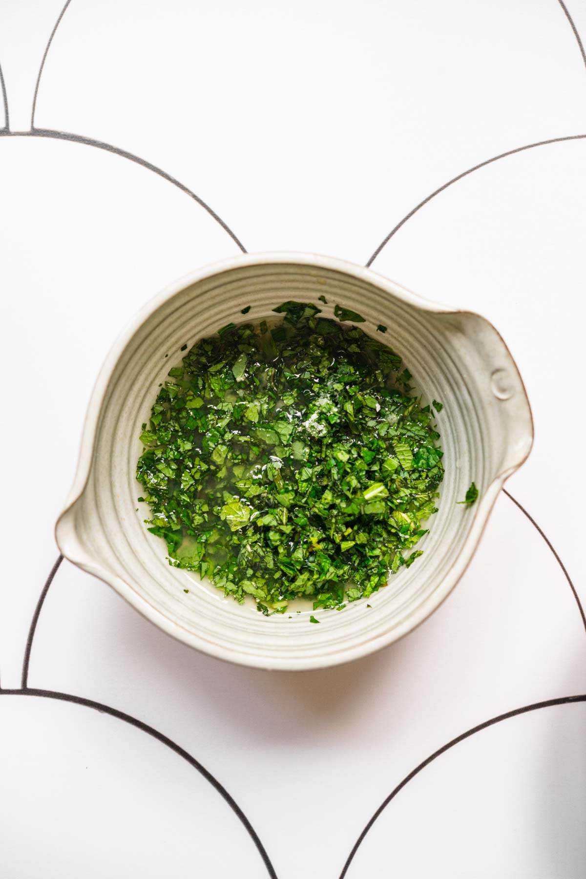 close up overhead view of lime mint dressing in white bowl.