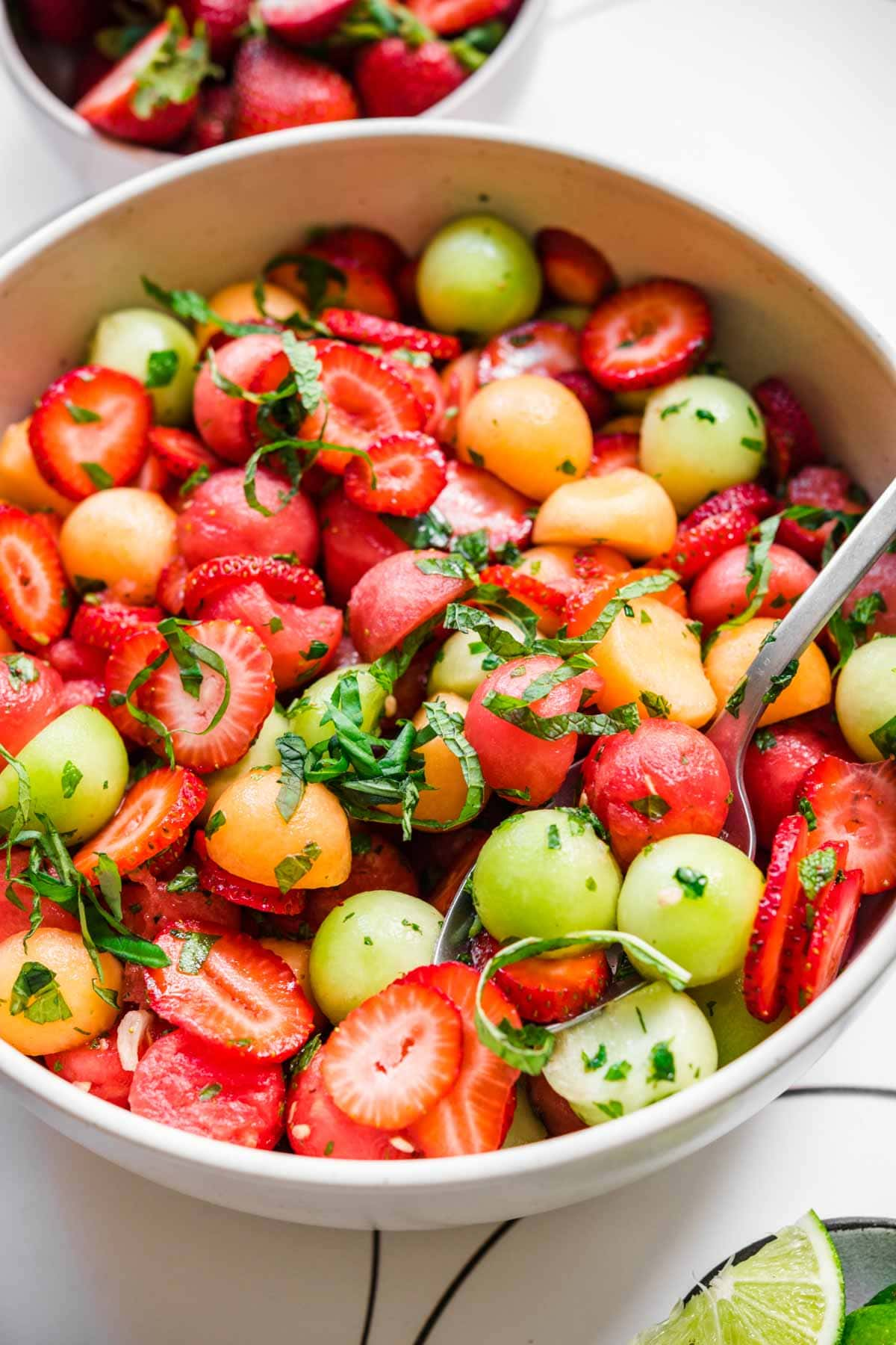 close up side view of melon ball salad with strawberries and mint in white bowl.
