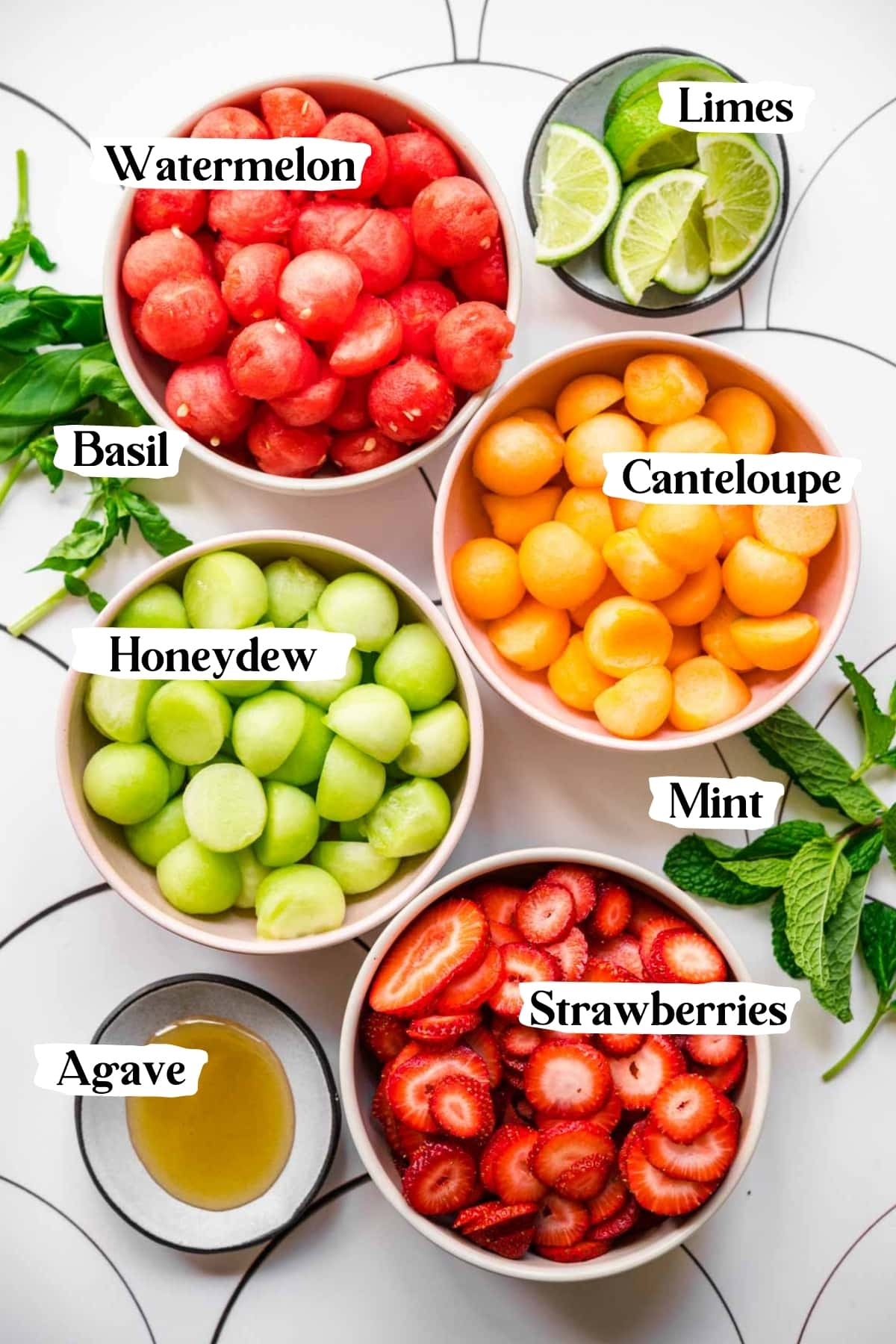 overhead view of ingredients for melon ball salad in bowls.