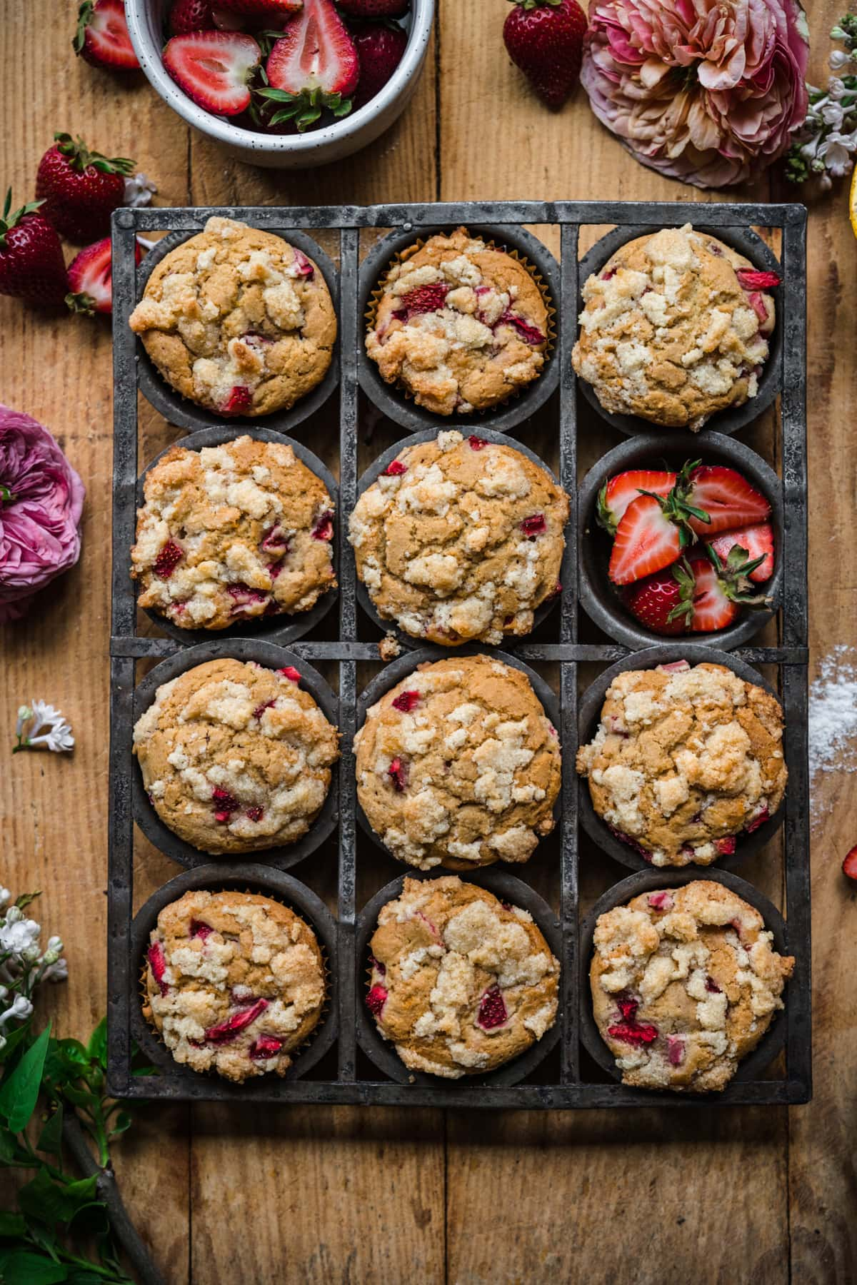 overhead view of vegan strawberry muffins with almond streusel in antique muffin tin on wood surface.