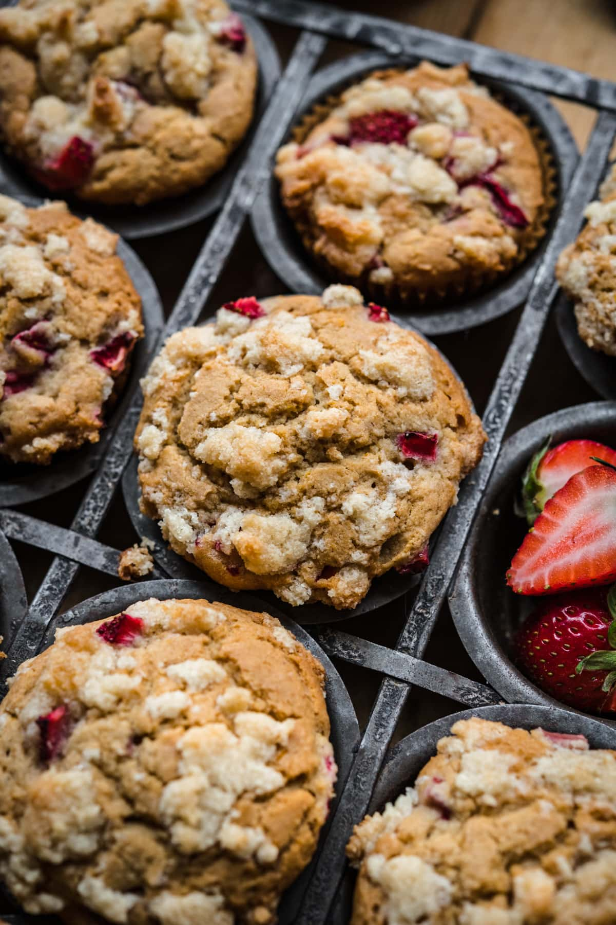 close up view of vegan strawberry muffins in tin with streusel on top.