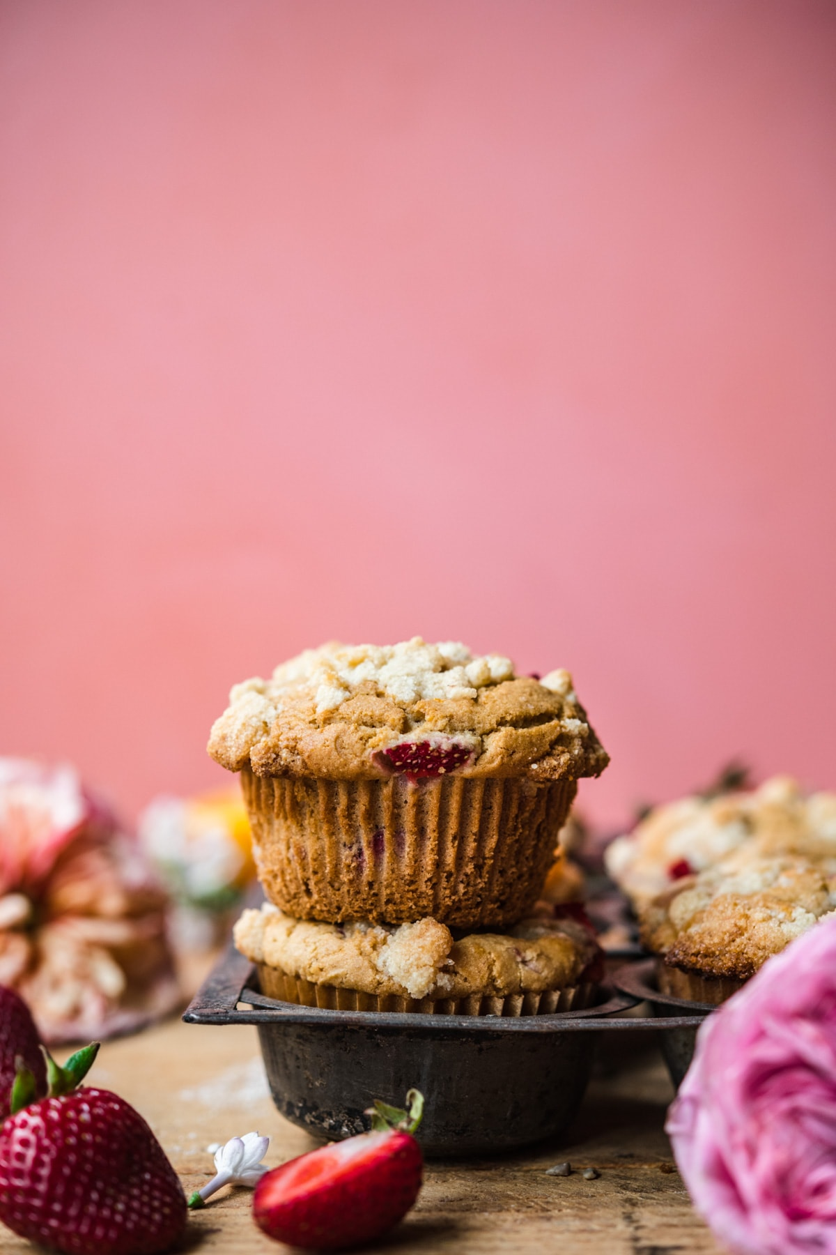 side view of two stacked vegan strawberry muffins with pink backdrop.