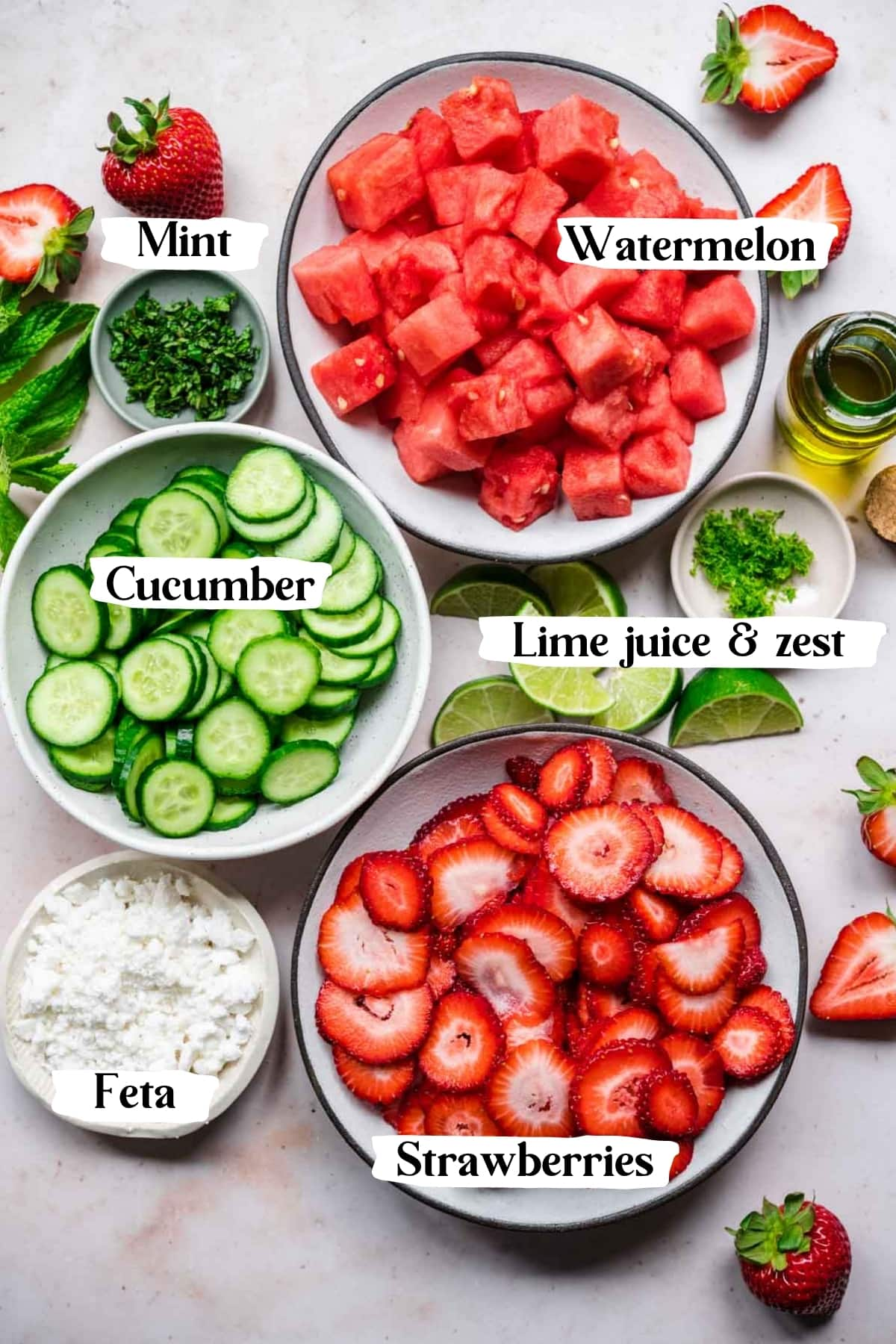 overhead view of ingredients for watermelon cucumber strawberry salad in prep bowls.