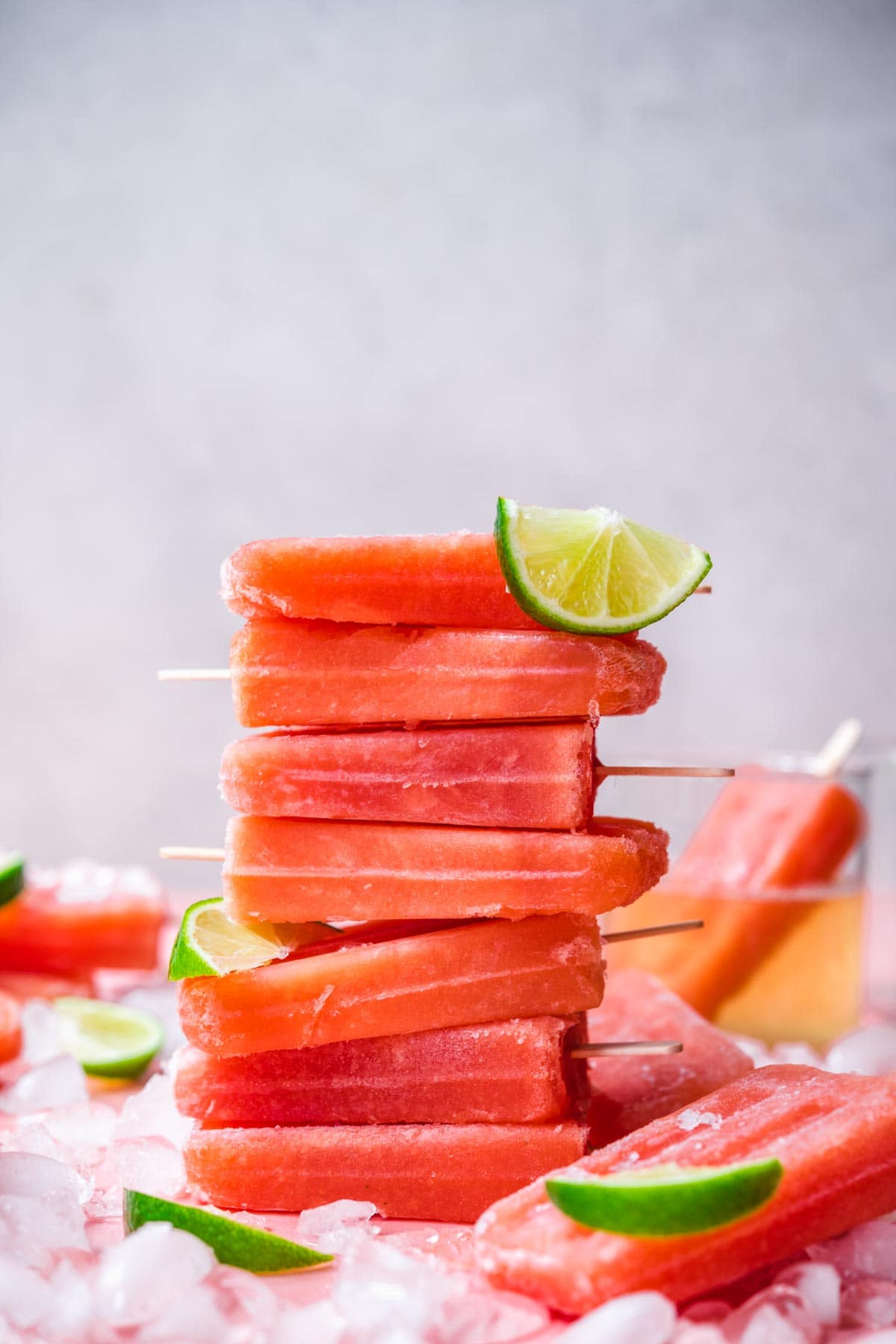 stack of watermelon prosecco popsicles with crushed ice and lime wedges.