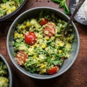 Green goddess salad in a bowl with a spoon. Full of quinoa and cherry tomatoes.