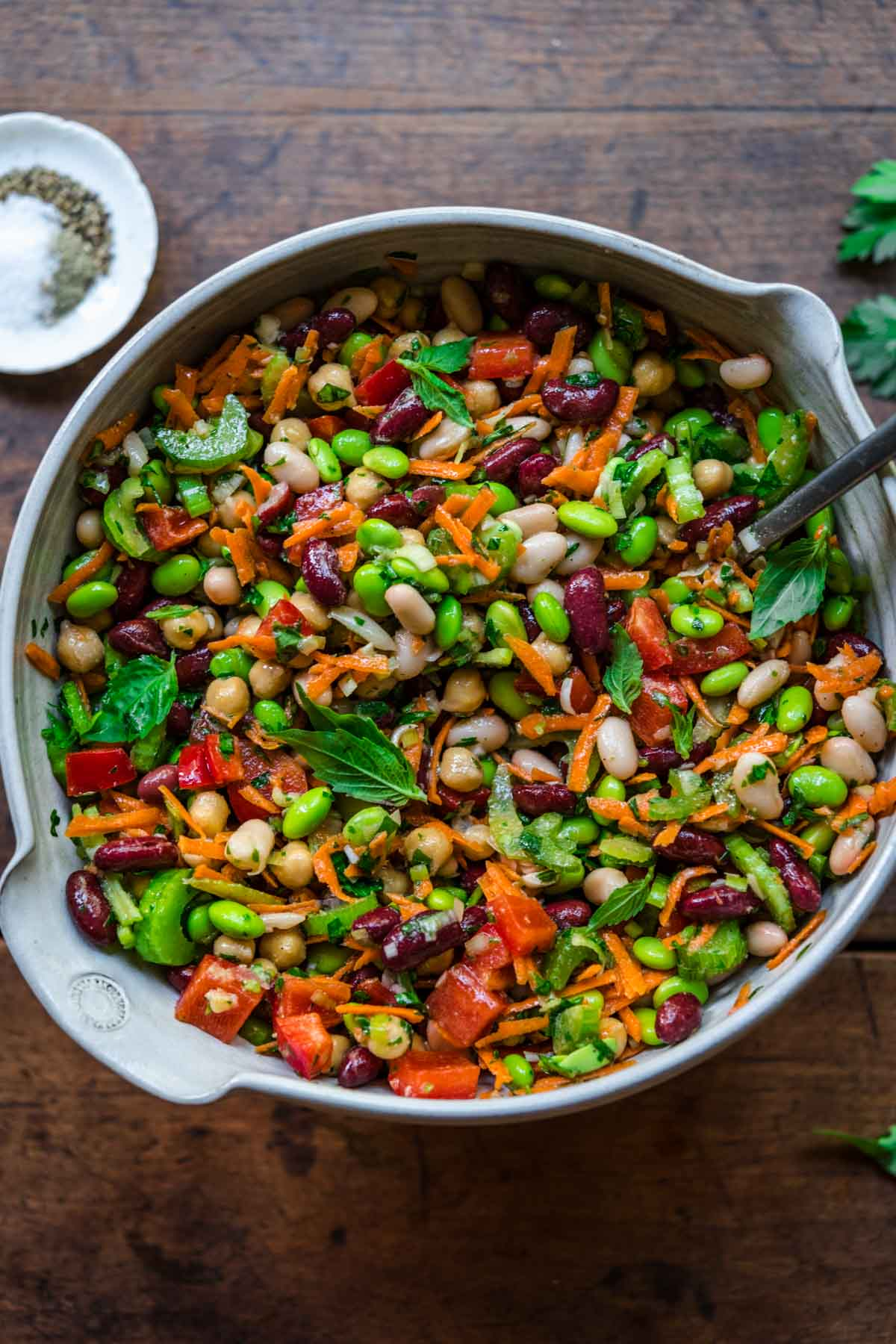 close up view of four bean salad in a large white mixing bowl on wood table.