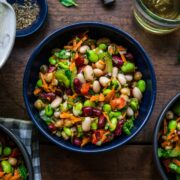 close up view of four bean salad in a blue bowl on wood table.