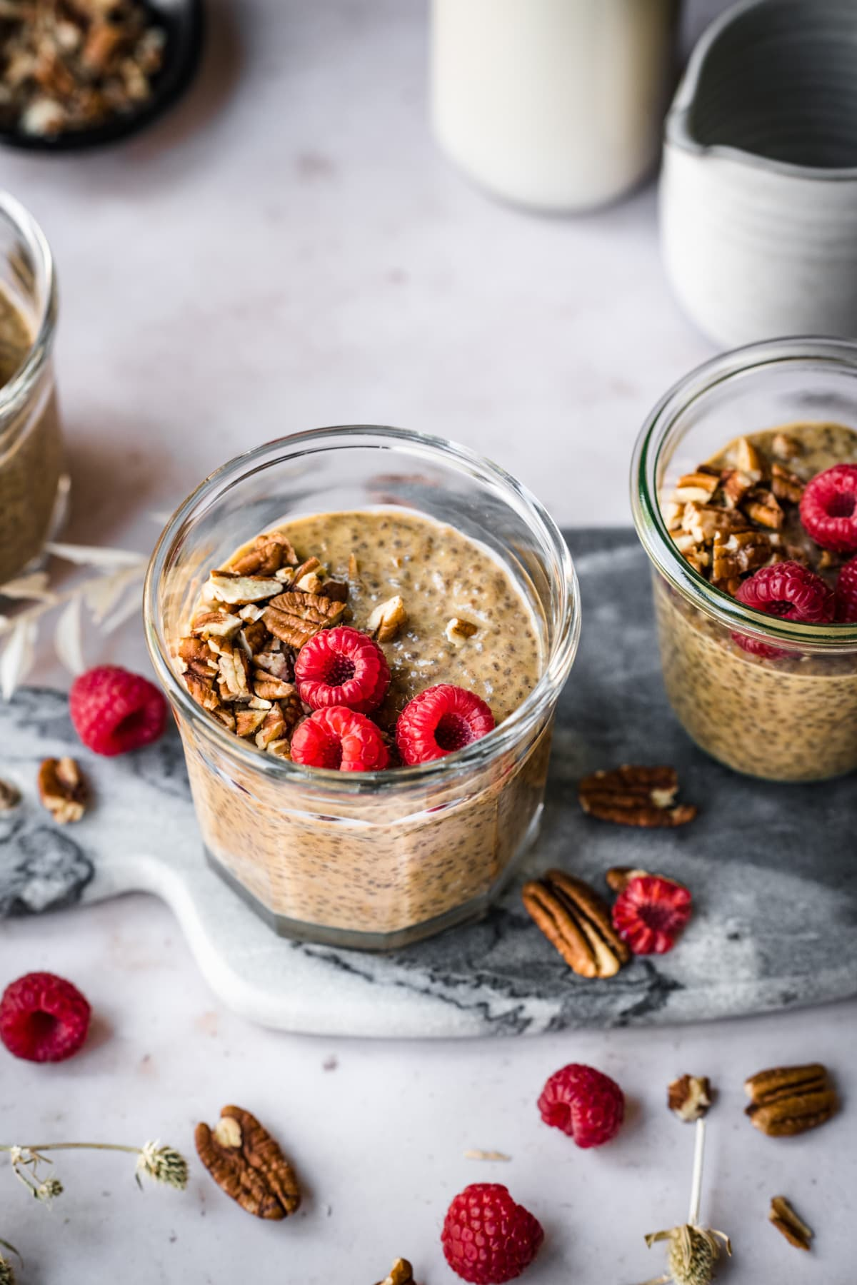 close up view of vegan pumpkin chia pudding in small jars topped with pecans and raspberries.