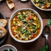 close up overhead view of summer minestrone soup in bowl with fresh basil on top.
