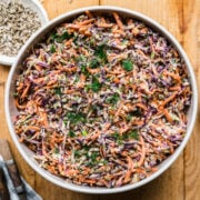 overhead view of large bowl of vegan coleslaw with serving spoon on wood table.