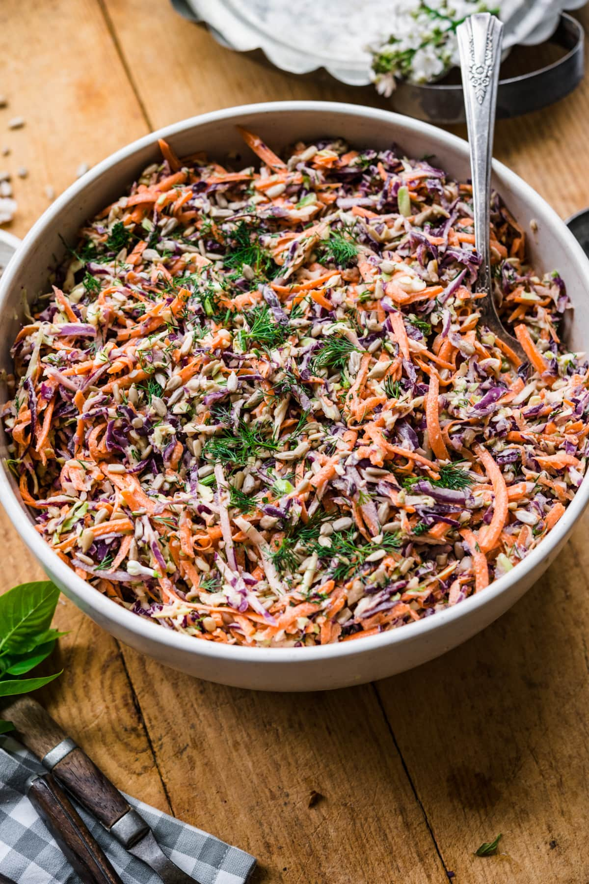 close up view of large bowl of vegan coleslaw with serving spoon on wood table.