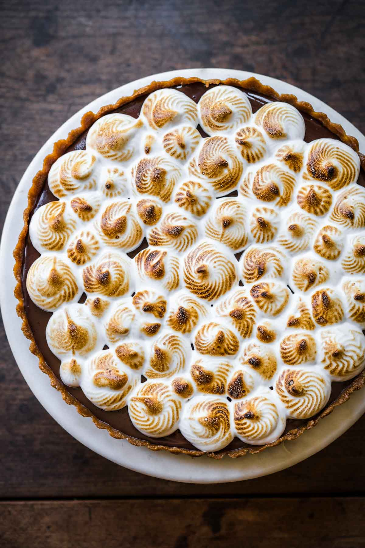 overhead view of vegan s'mores tart on cake stand.