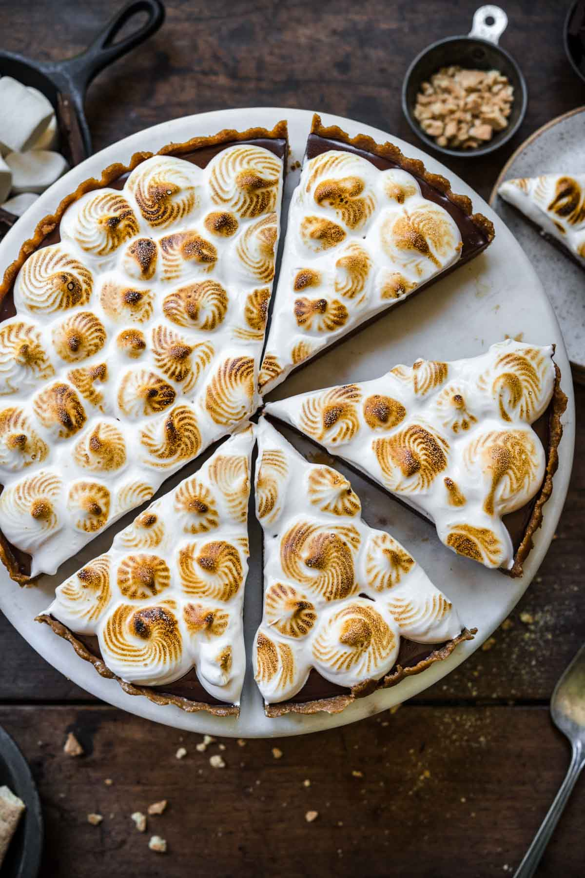 overhead view of sliced vegan s'mores tart on cake stand.