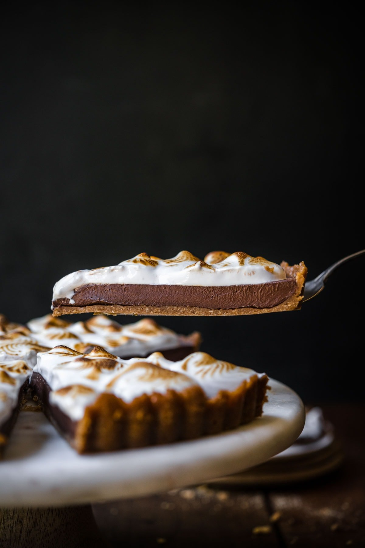 side view of person lifting up slice of vegan s'mores tart from cake stand.