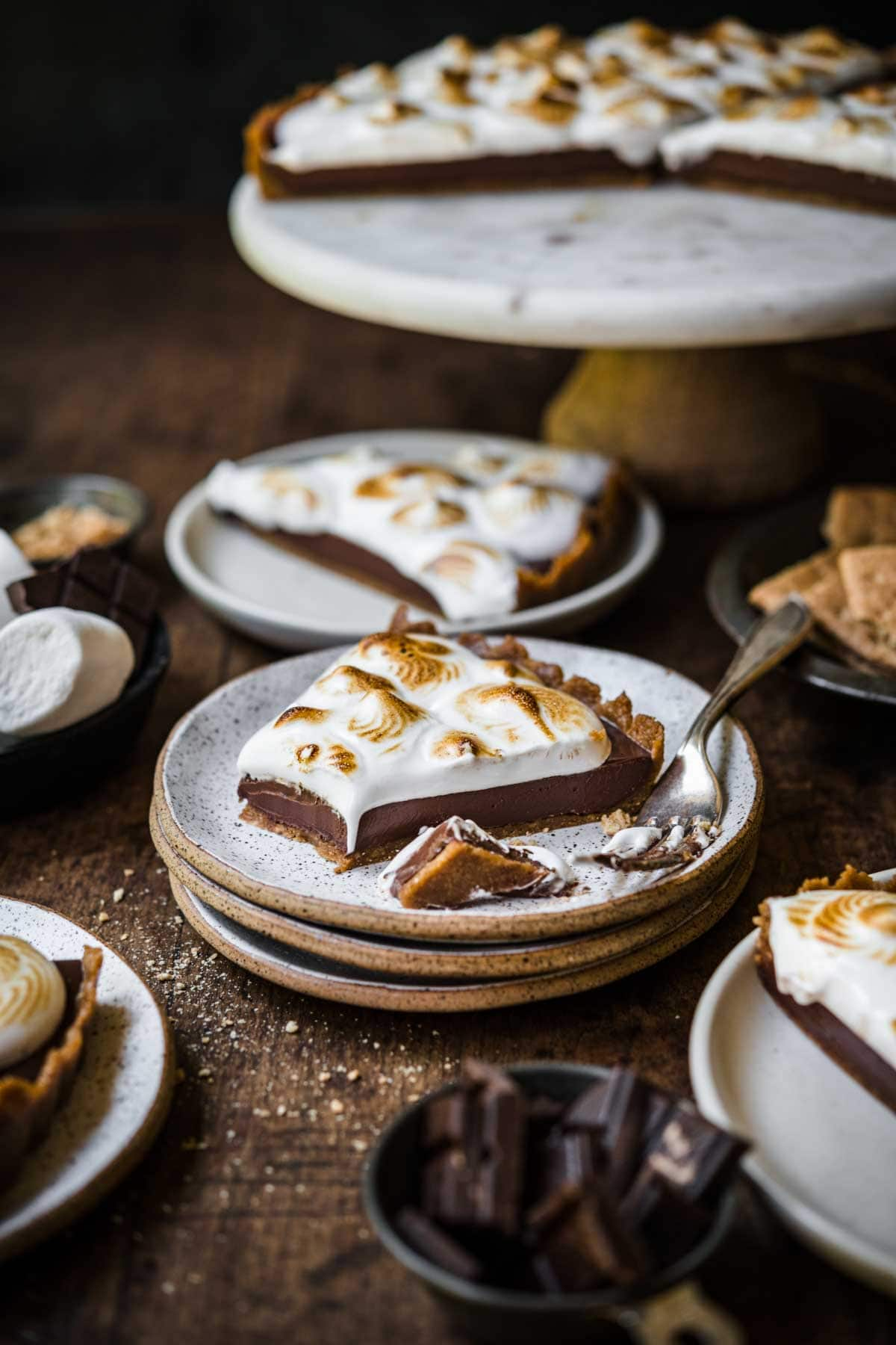 side view of slice of vegan s'mores tart on stack of plates on wood table.