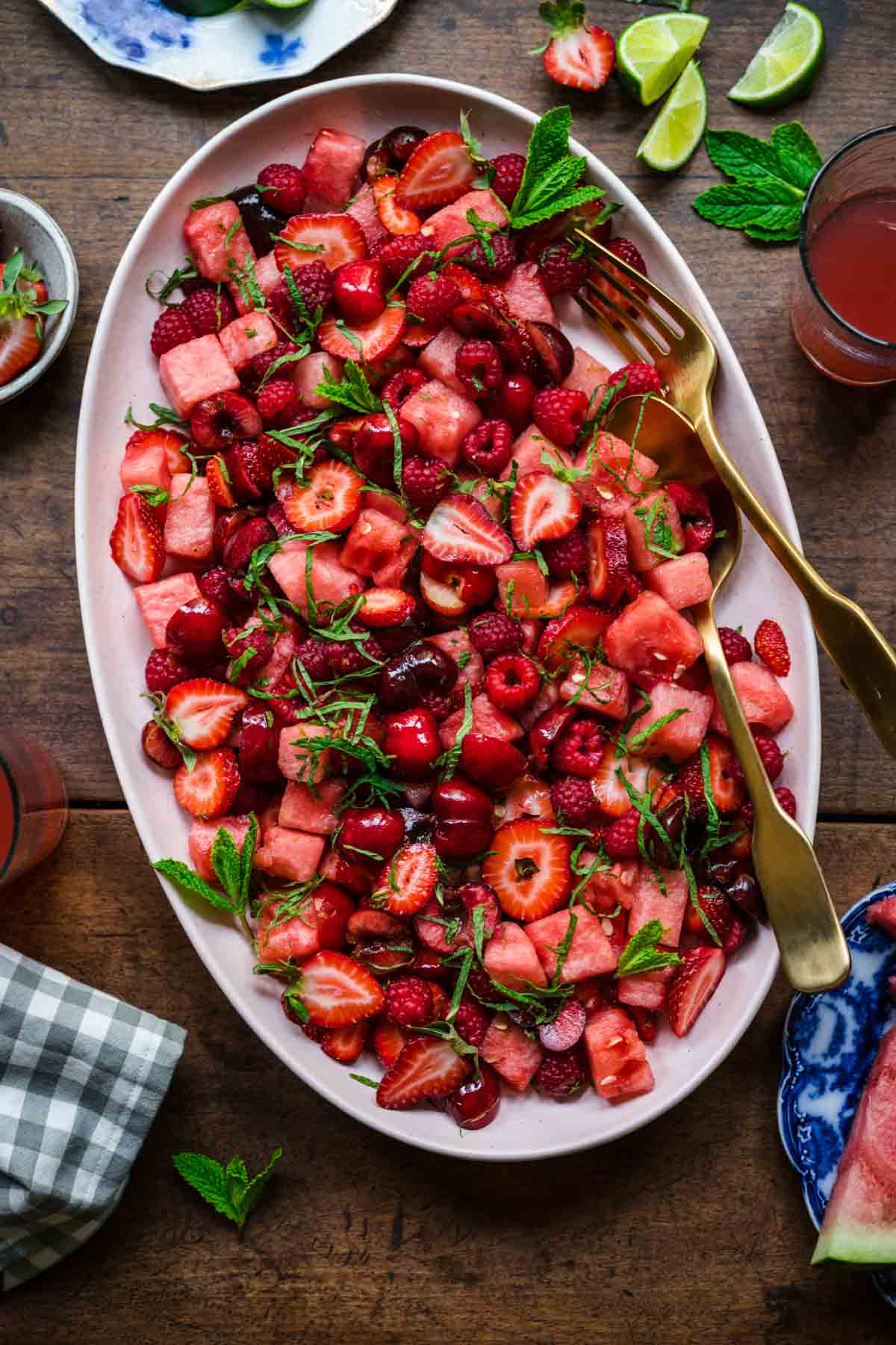 overhead view of watermelon berry salad with mint on a large platter on wood table.