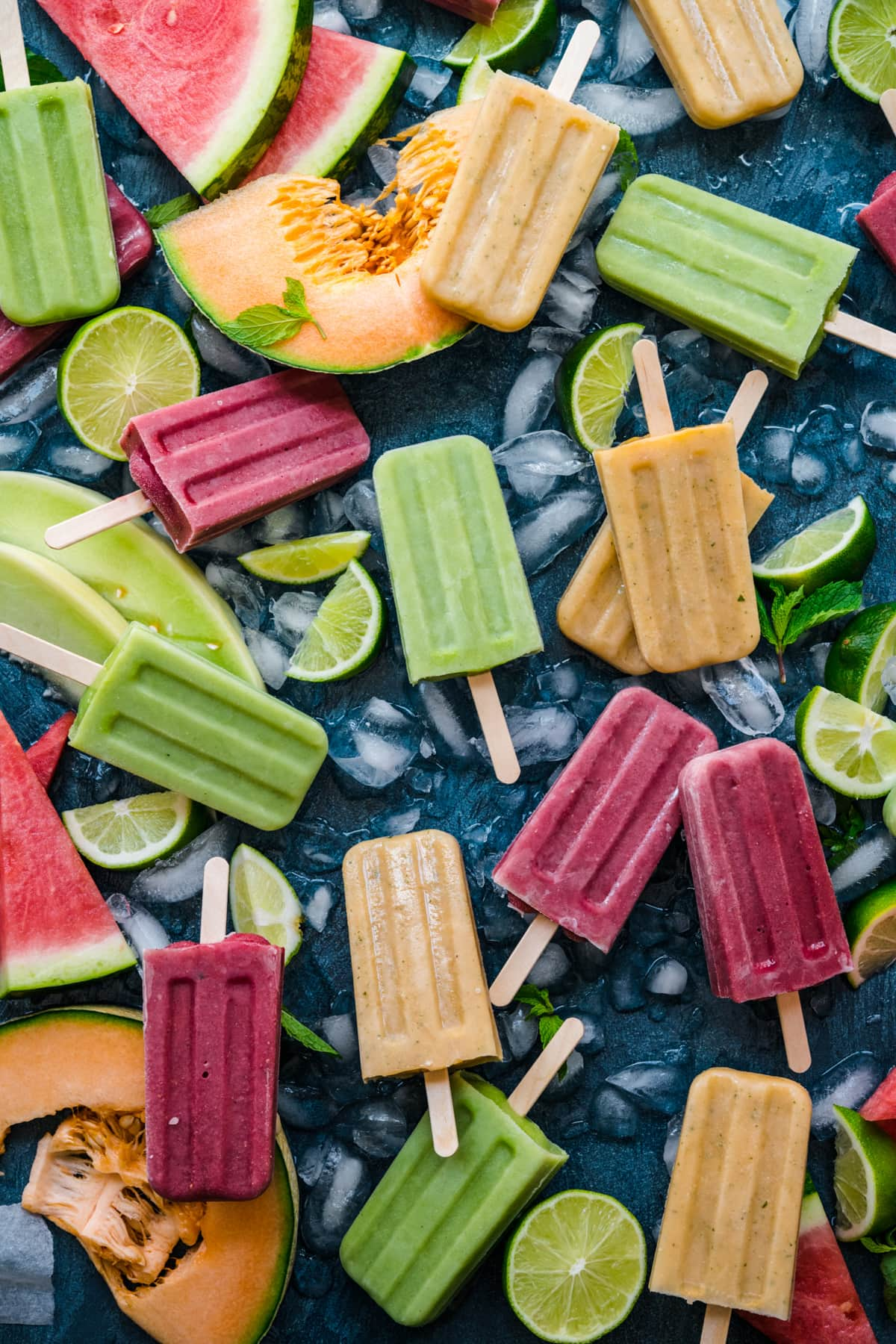 overhead view of watermelon, cantaloupe and honeydew melon yogurt popsicles on blue backdrop with fresh melon.