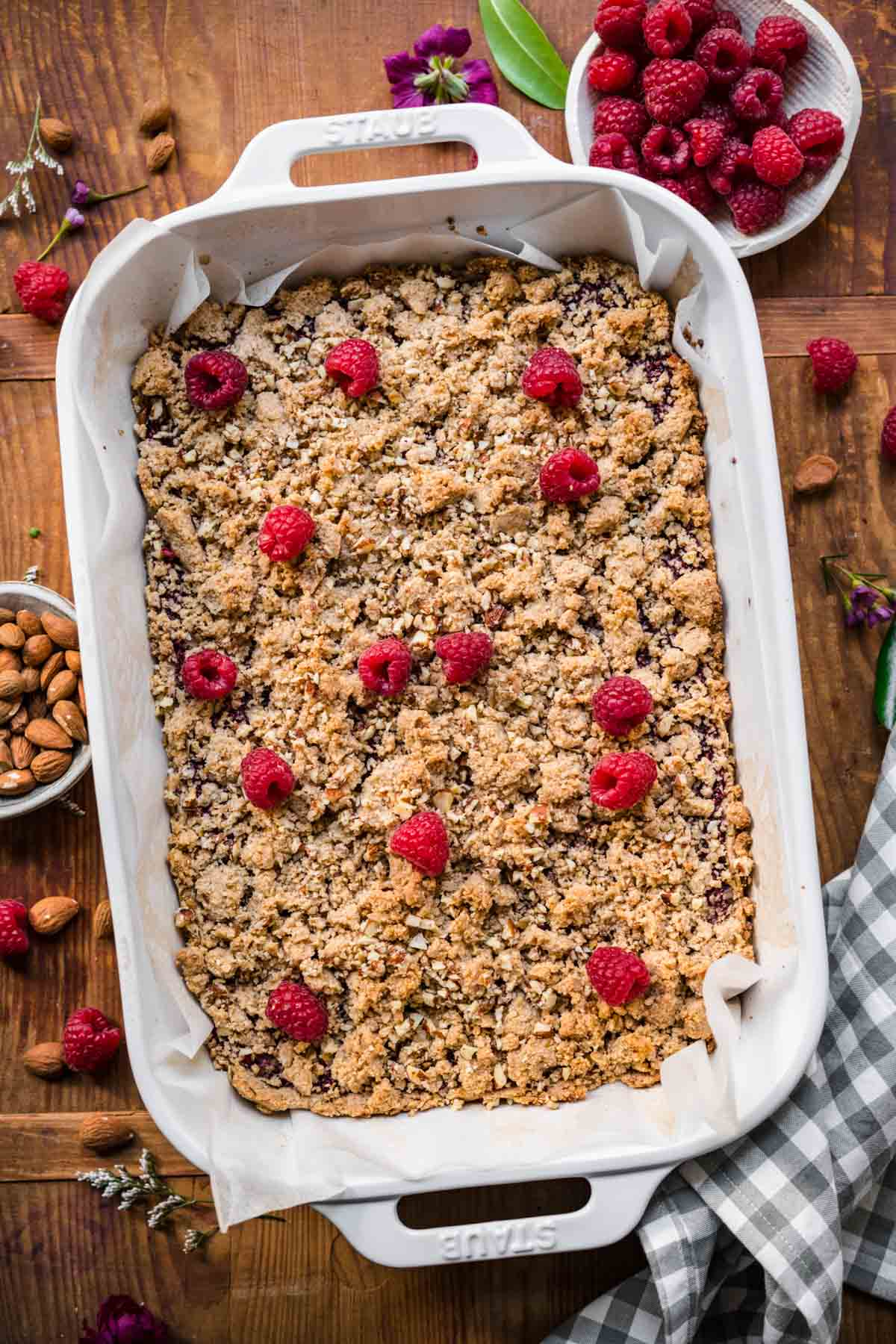 overhead view of raspberry crumble bars in white baking pan with fresh raspberries on top.