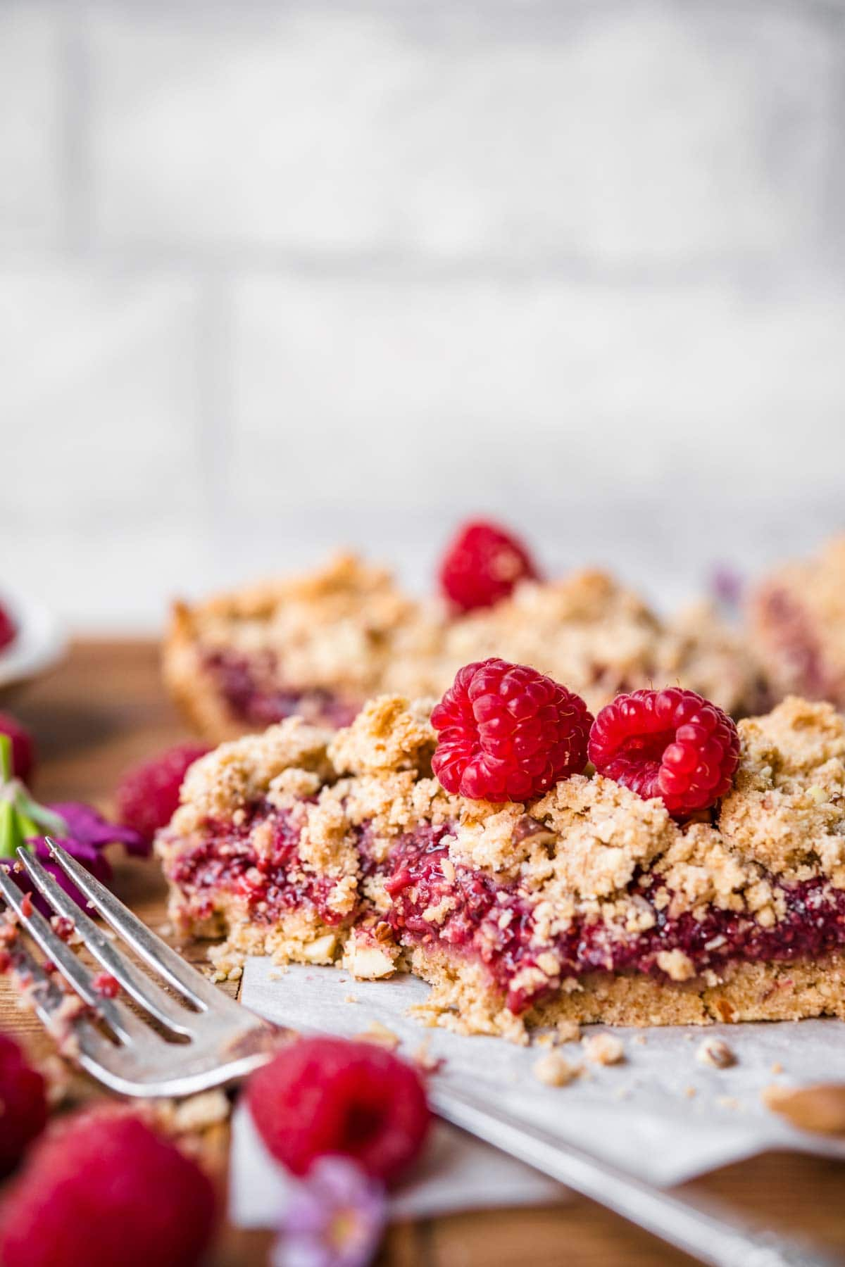 close up side view of raspberry crumble bar topped with fresh raspberries on parchment paper.