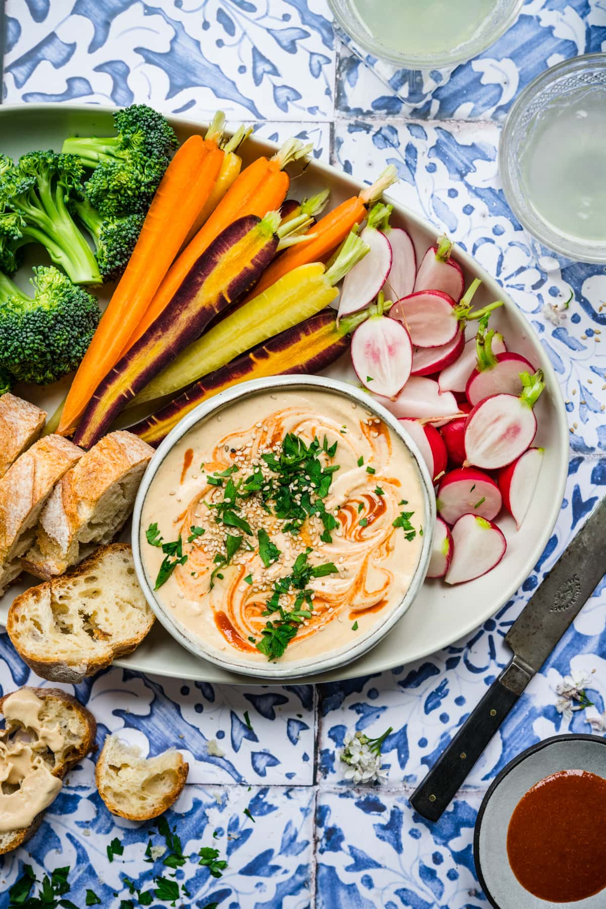 overhead view of sriracha white bean dip on a platter with fresh vegetables on blue tile backdrop.