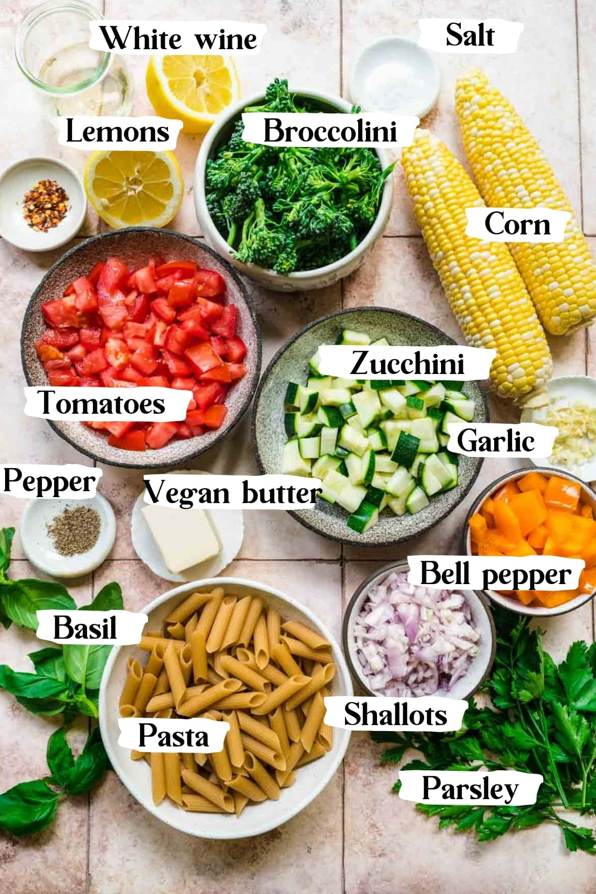 overhead view of ingredients for vegan summer vegetable pasta in small bowls.