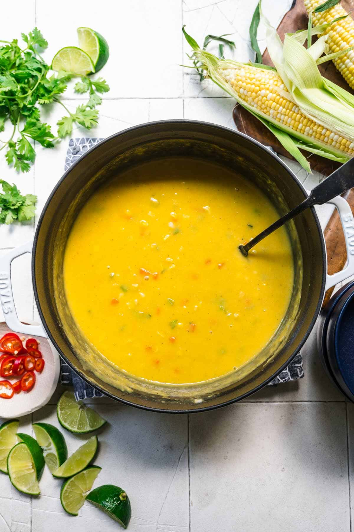 overhead view of vegan corn chowder in large soup pot on white tile background.