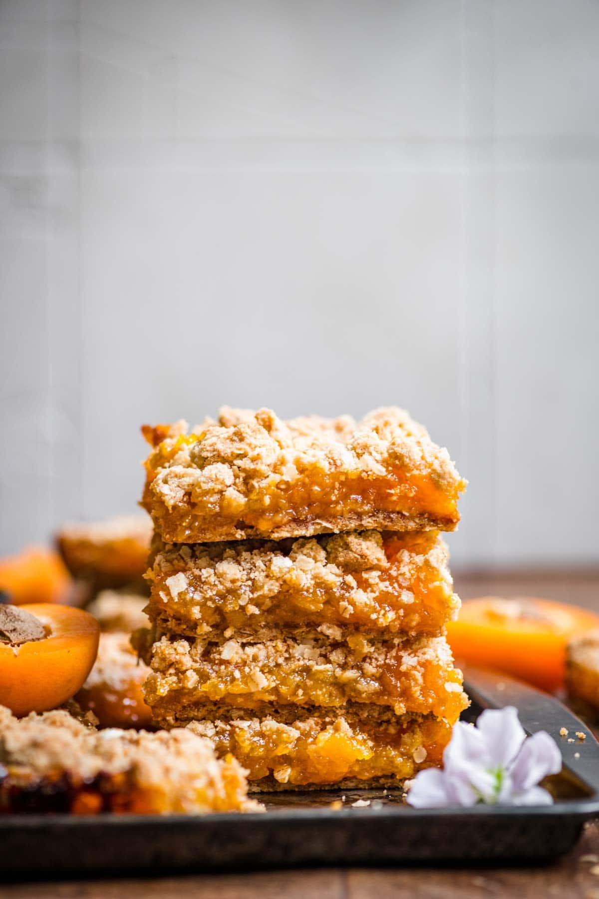 4 crumble bars stacked on top of one another with apricots spread throughout the background.