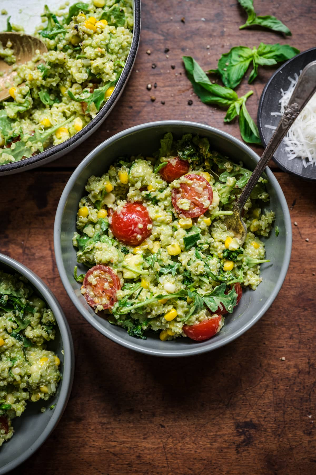 Green goddess salad in bowl. Full of quinoa, corn, and cherry tomatoes.