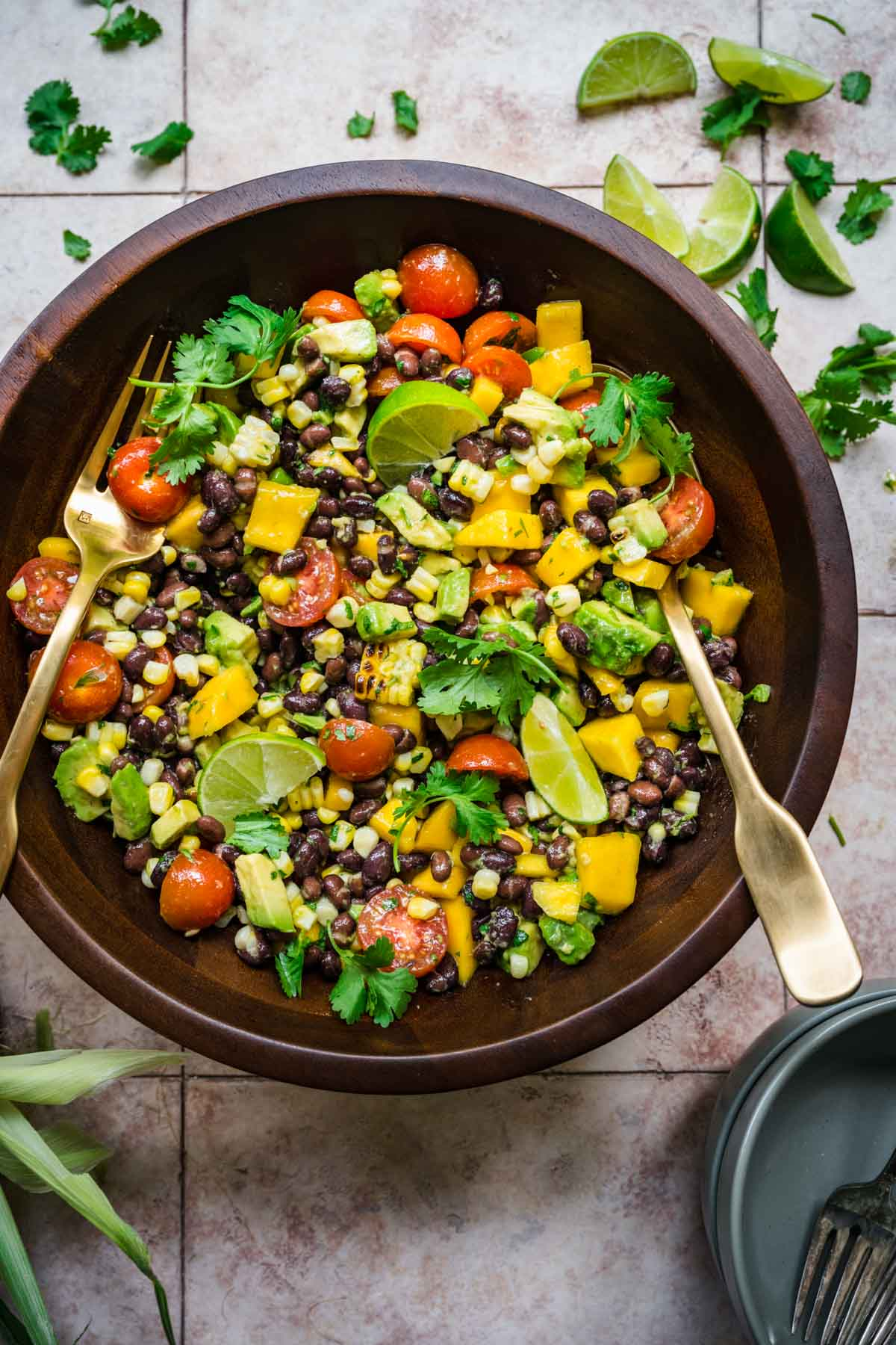 Black bean and mango salad seen from above in a wooden bowl with a fork and a spoon.