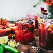 side view of blackberry peach cocktail with summer flowers.