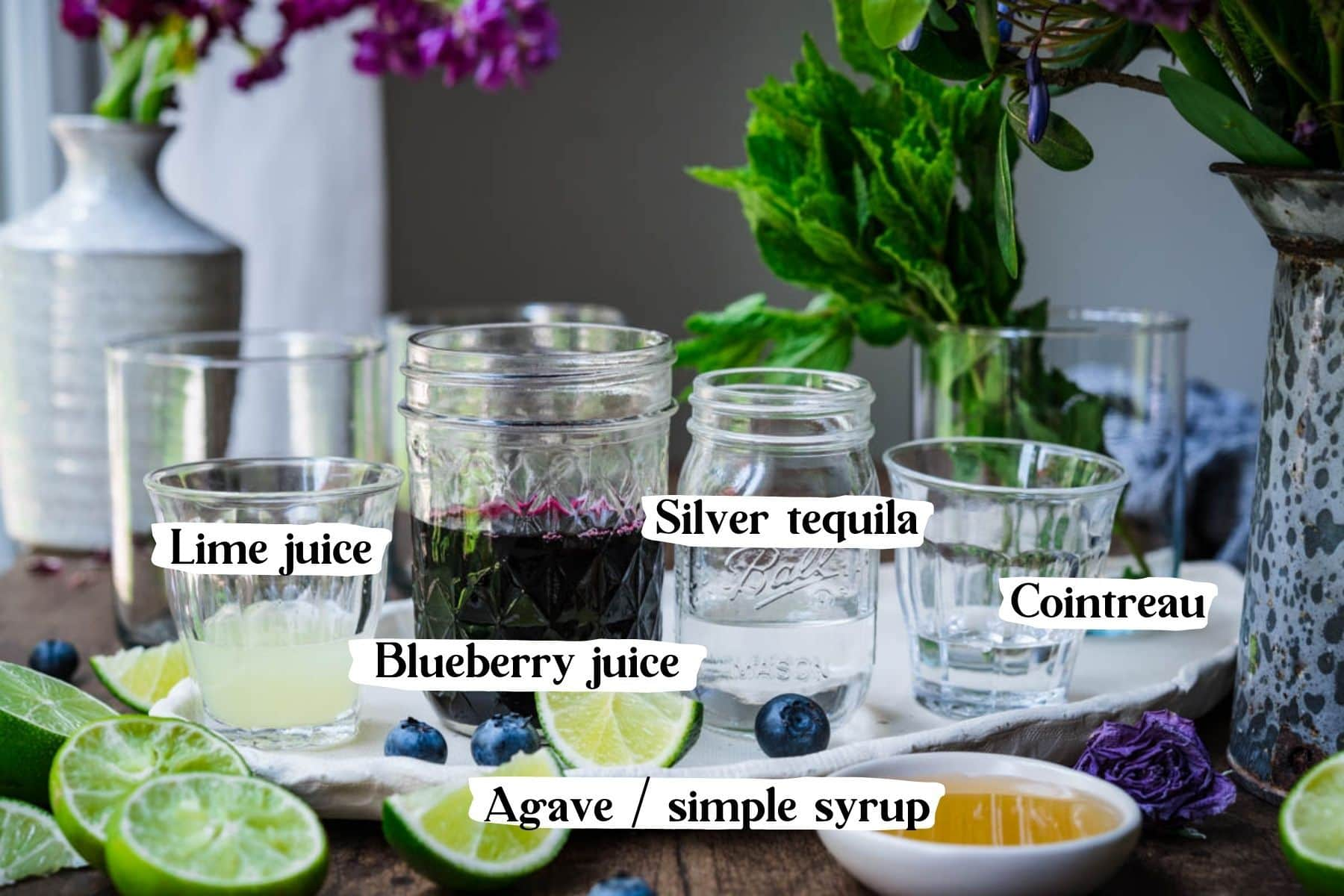 Front view of cocktail ingredients, including lime juice, blueberry juice, silver tequila, cointreau, and agave.