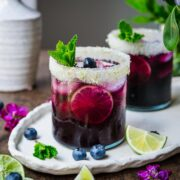 Blueberry margarita in a glass with a salted rim, garnished with mint, blueberries, and lime.