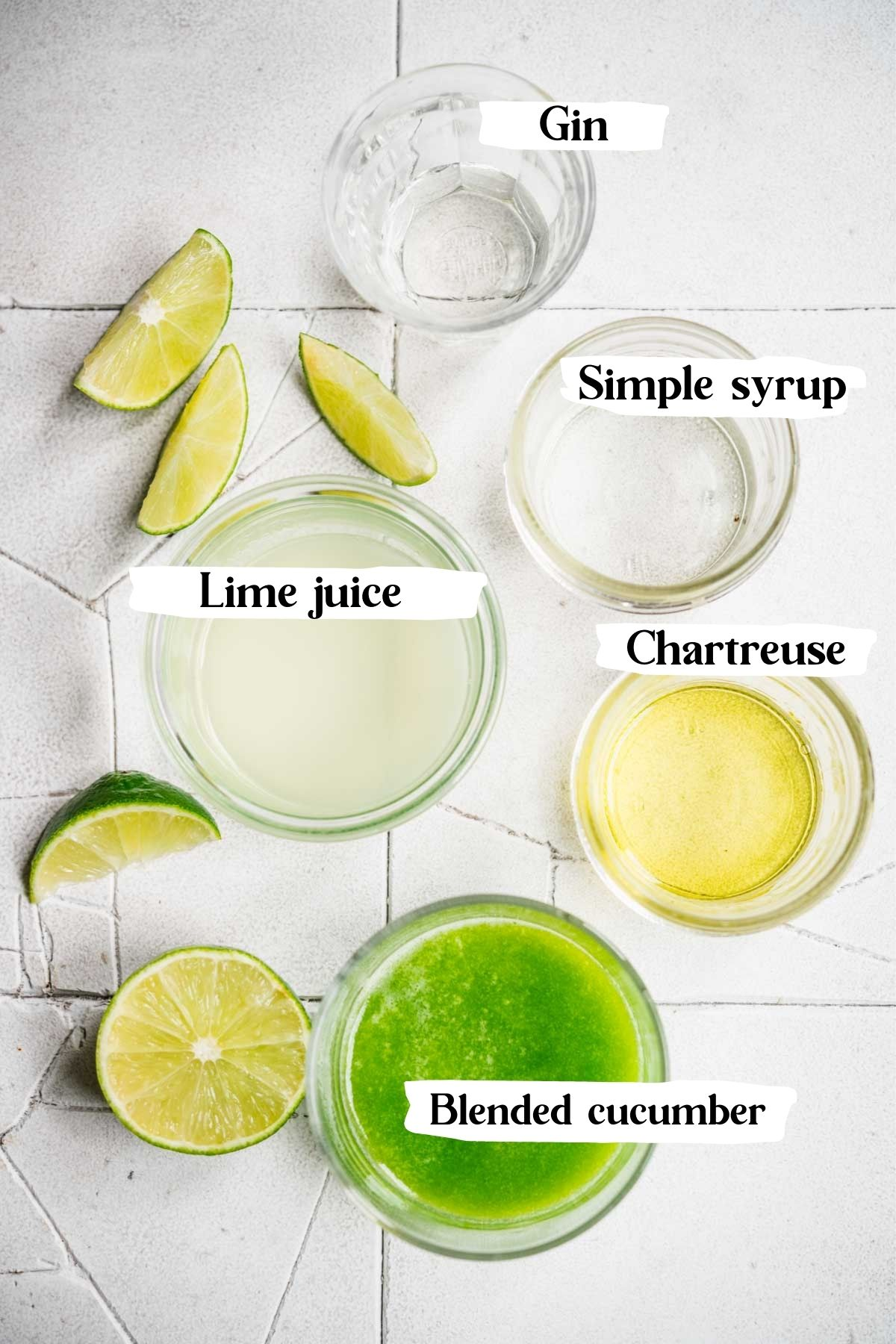 Shot of cucumber lime cocktail ingredients - lime juice, blended cucumber, chartreuse, gin, simple syrup.