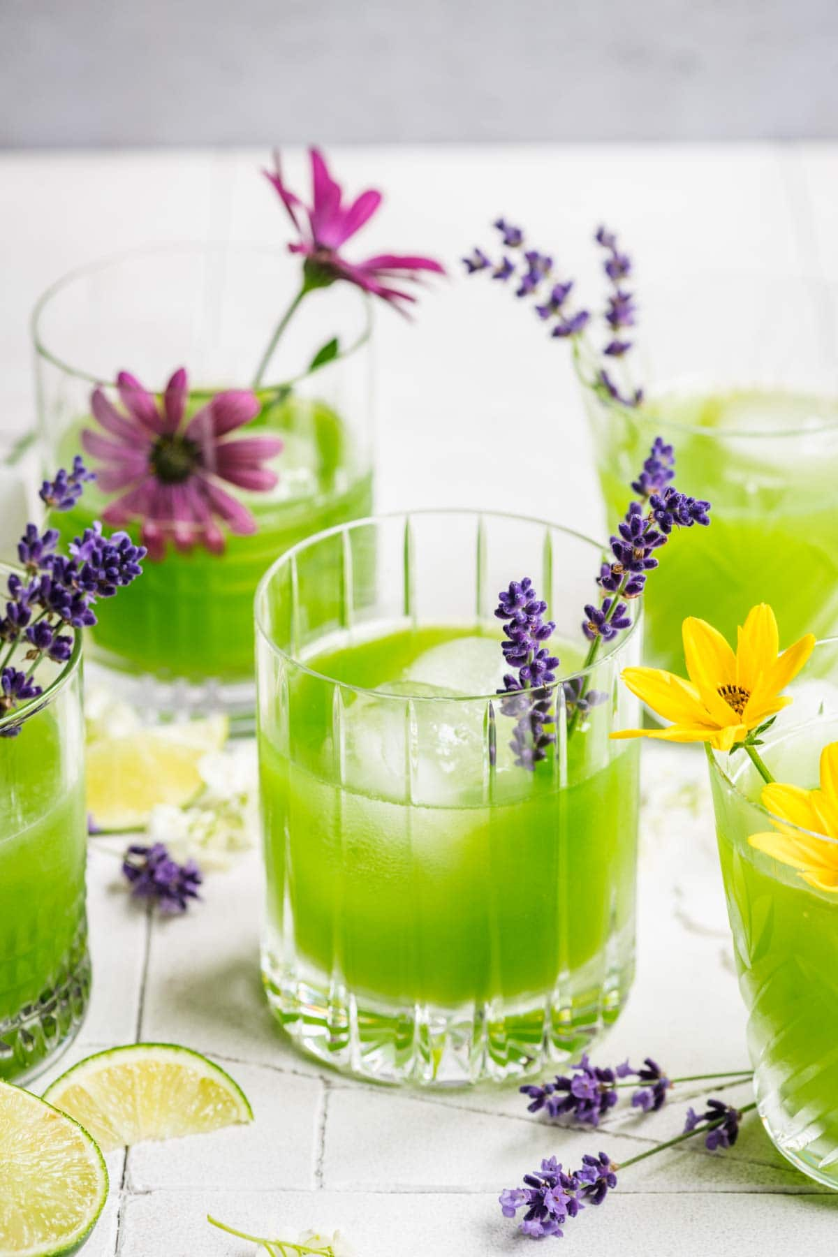 Cucumber gin cocktail in a glass with ice, garnished with a sprig of lavender.