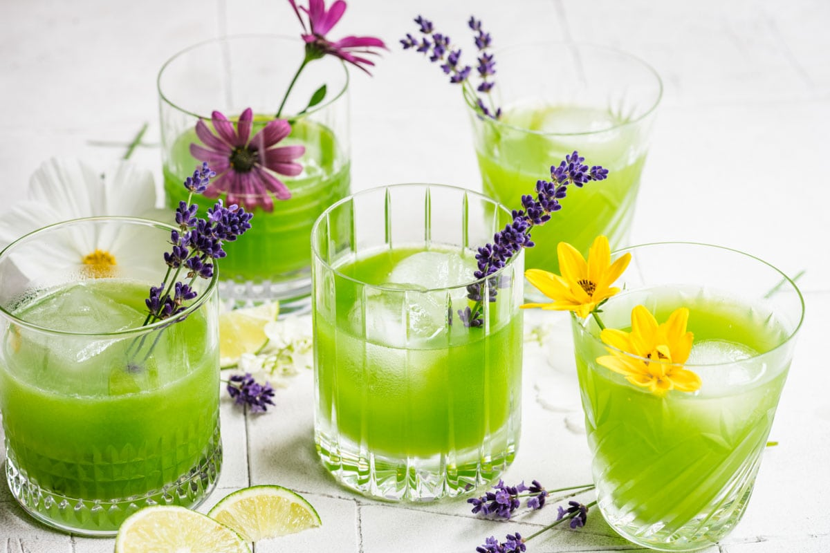 5 cucumber cocktails in varied glasses, garnished with flowers.