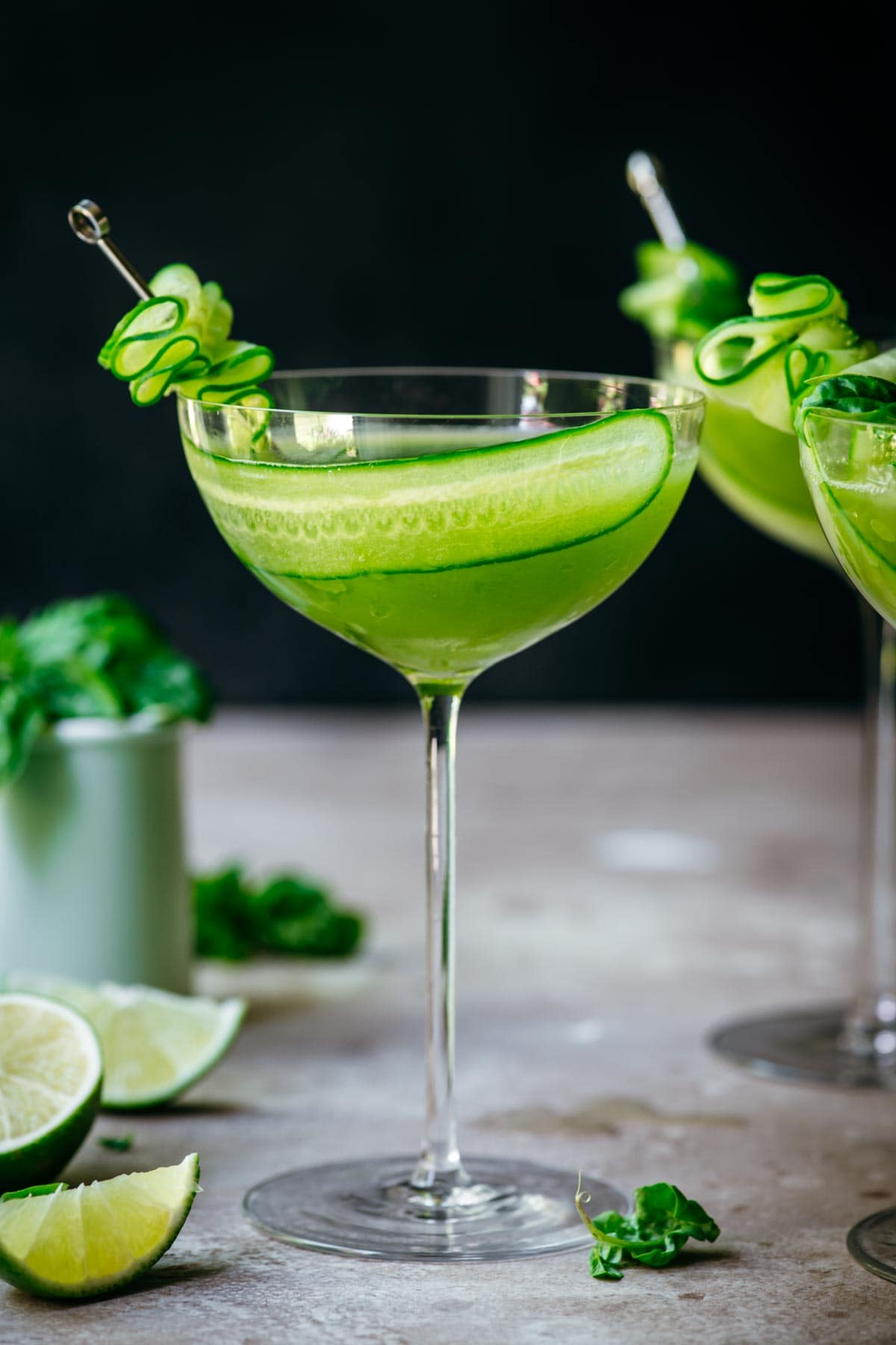 Front view of cucumber martini in a martini glass, garnished with cucumber.