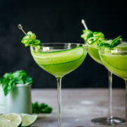 Front view of cucumber martini in a glass garnished with a slice of cucumber.