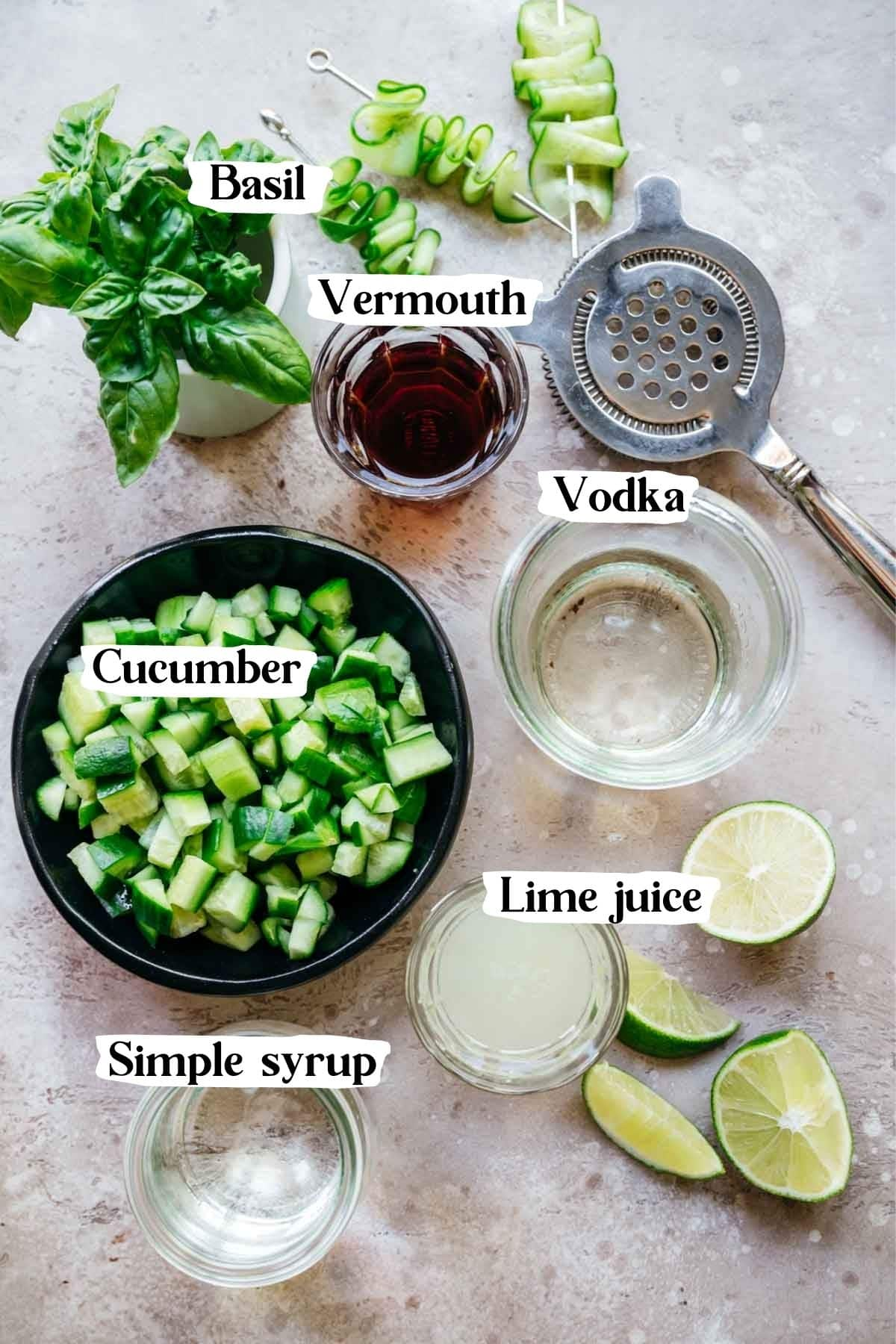 Overhead shot of ingredients needed in this recipe, including vodka, cucumber, simple syrup, basil, and vermouth.