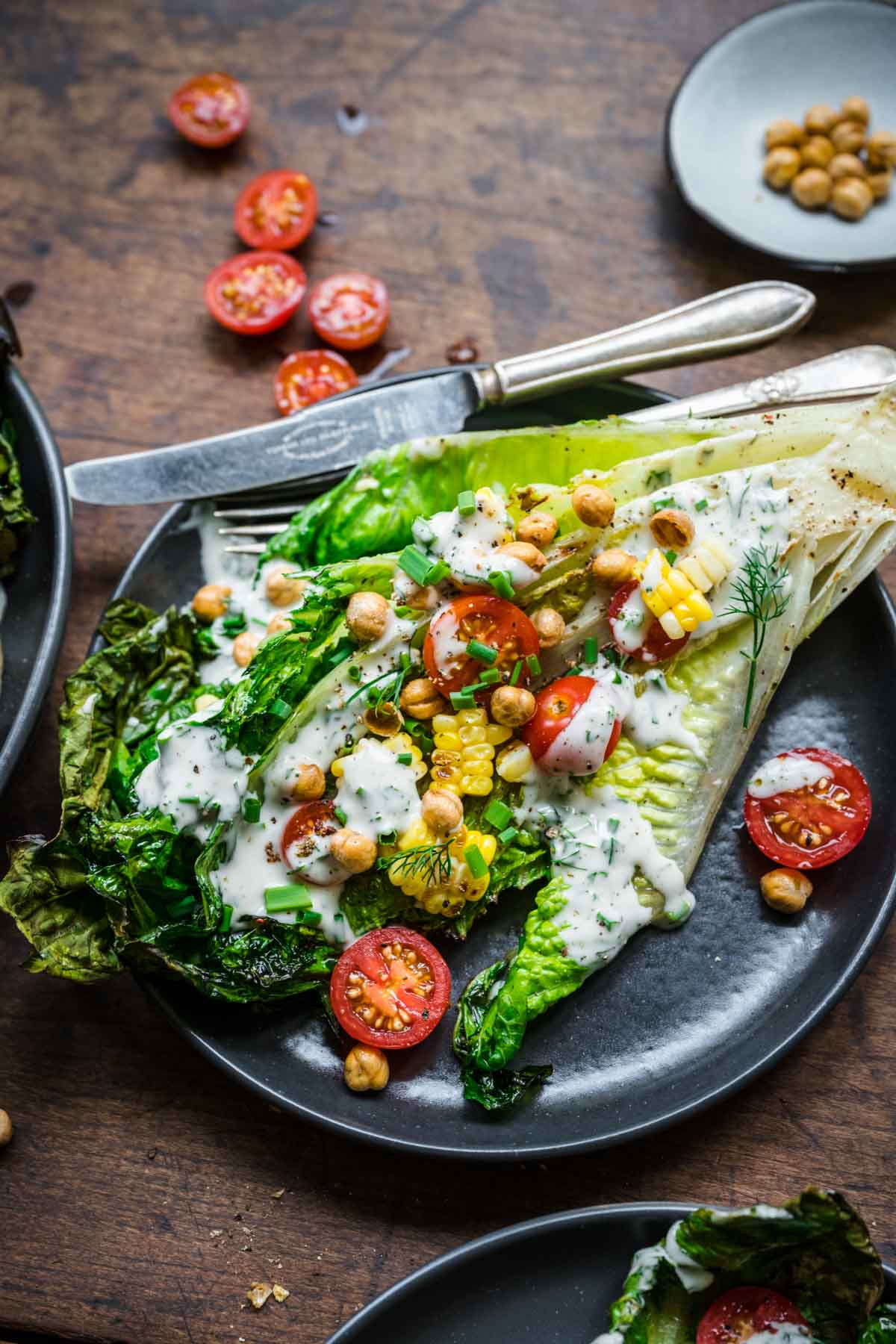 Overhead view of grilled romaine with corn, tomatoes, and vegan ranch dressing.