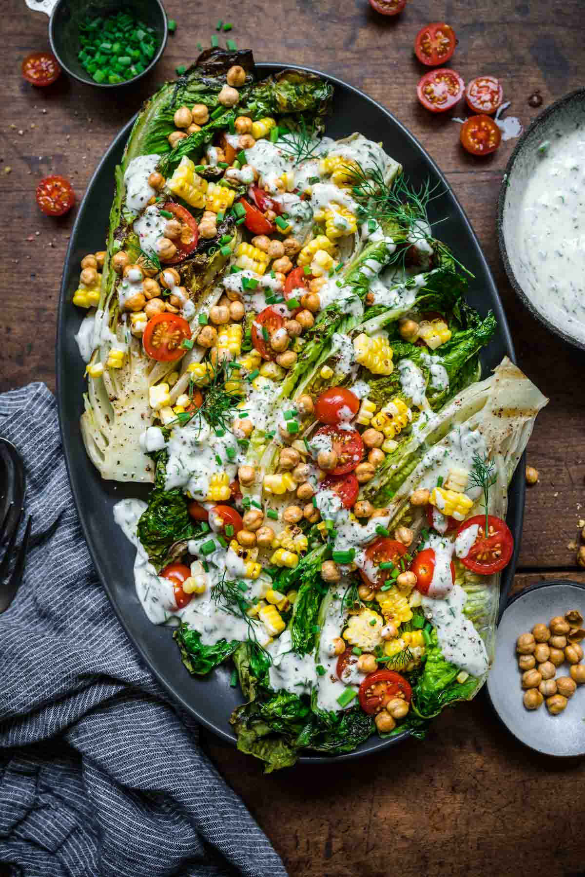 Overhead view of 4 heads of grilled romaine with crispy chickpeas, corn, tomatoes, and vegan ranch.