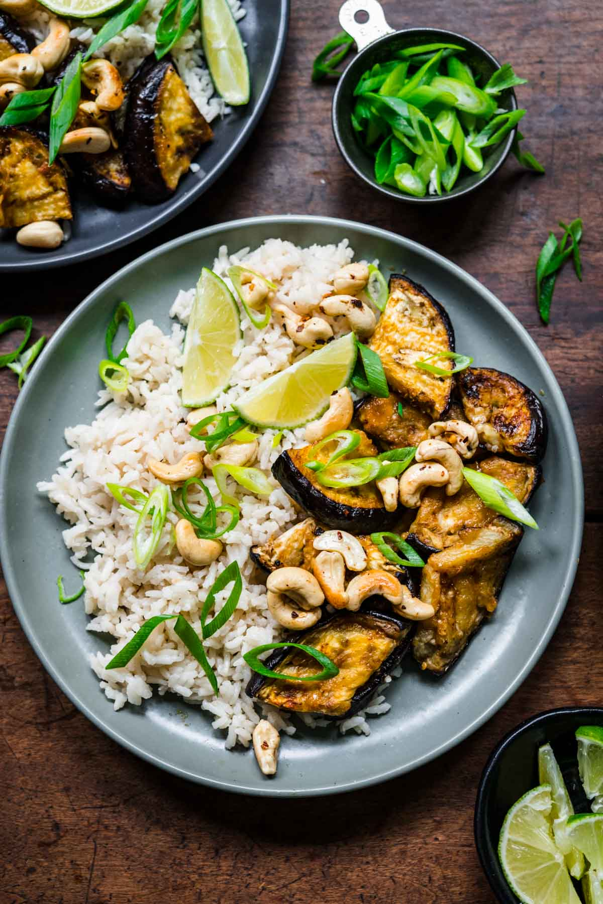Overhead view of eggplant and rice on a plate, garnished with green onions, cashews, and lime.