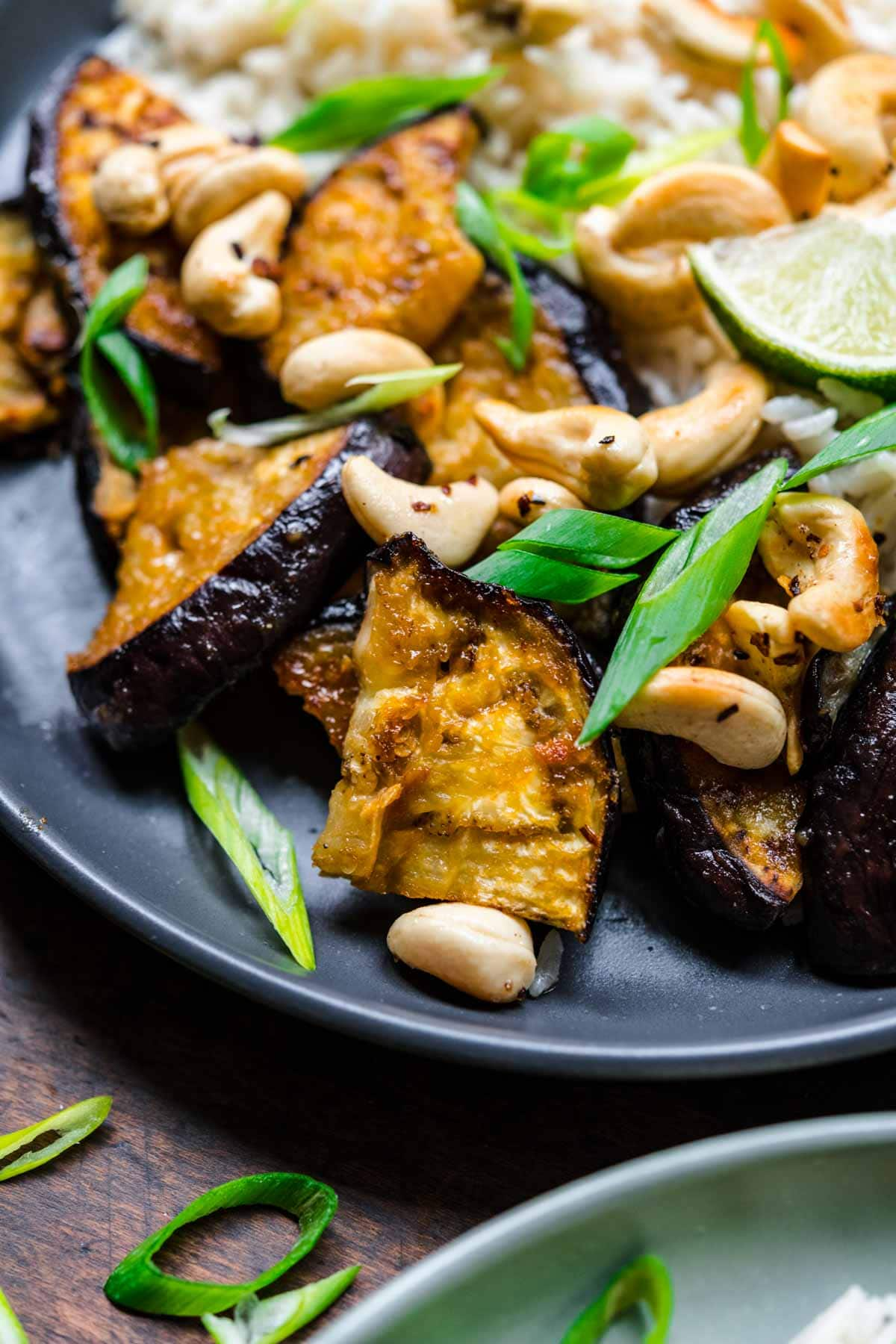 Close up of eggplant on a plate with cashews and green onions.