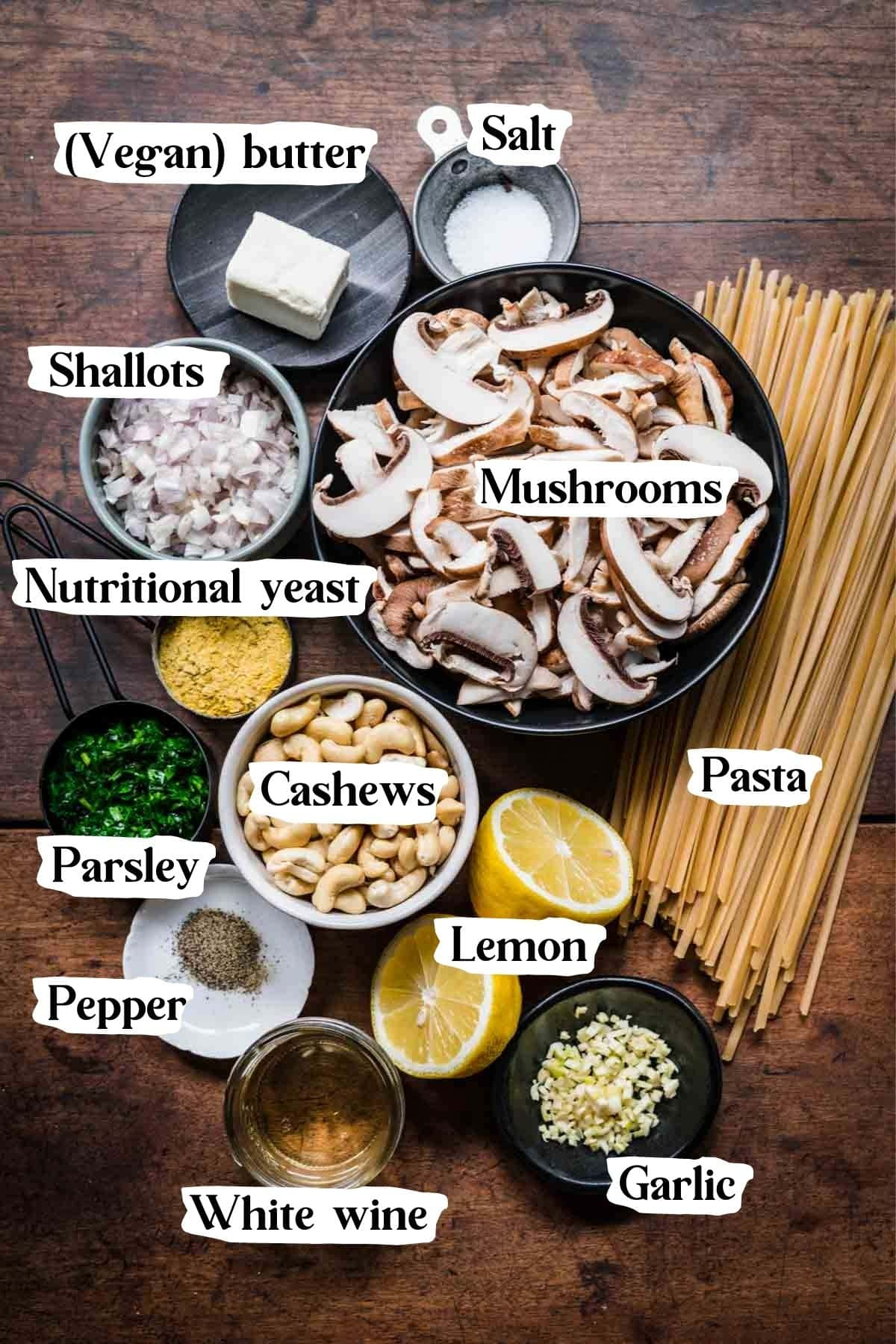 Overhead view of mushroom alfredo ingredients, including pasta, mushrooms, cashews, and parsley.